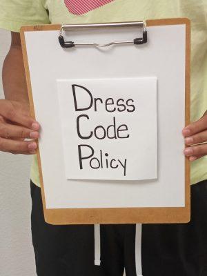 Alex Alvarez holding dress code sign